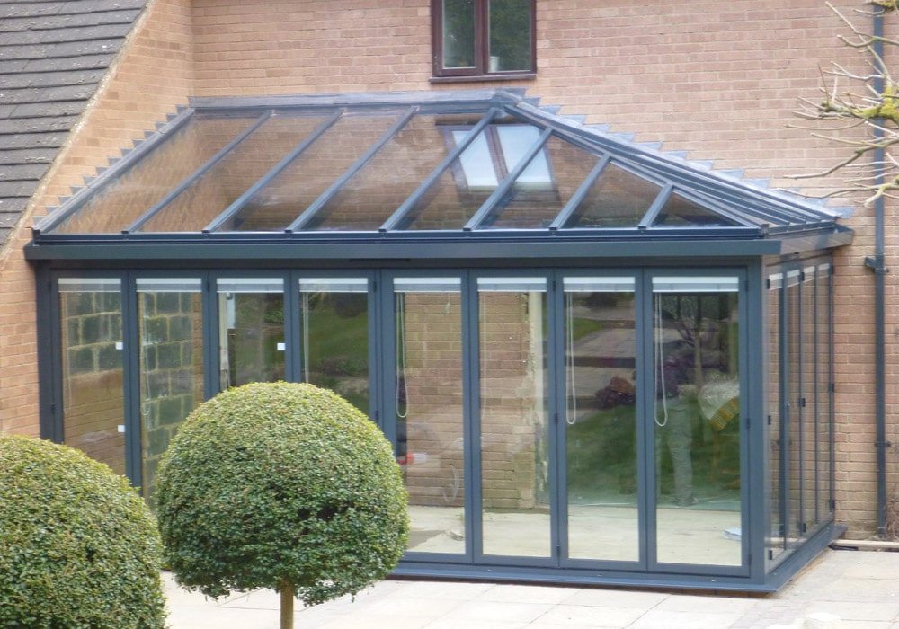 Hipped glass roof with bifold doors below