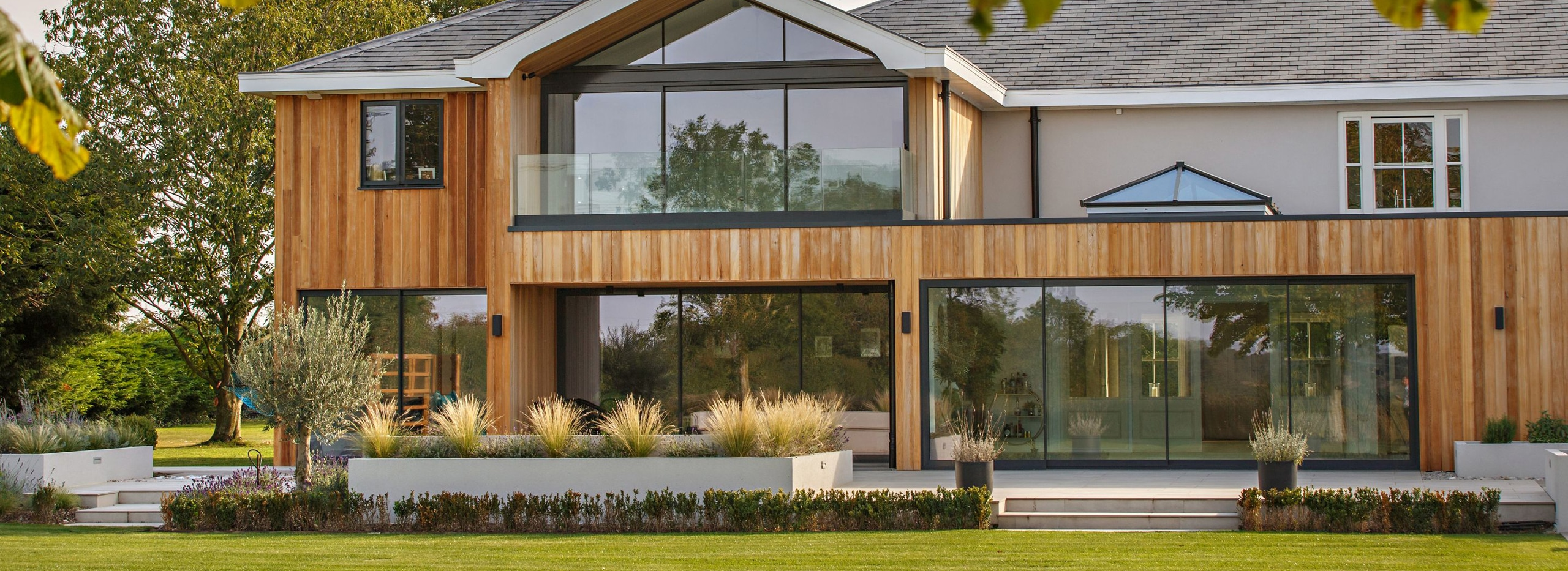 Large glazed sliding doors on timber clad home in Norfolk
