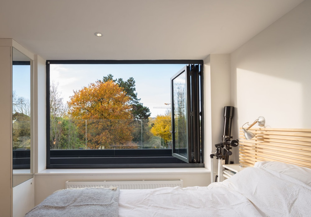This three panel bifold window open out from this master-bedroom in a loft conversion