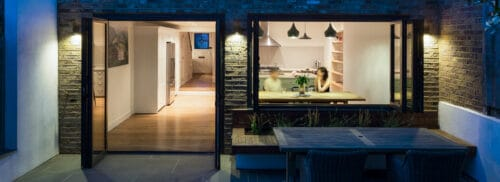 This stylish kitchen and outdoor seating area are joined by a bifold window and door