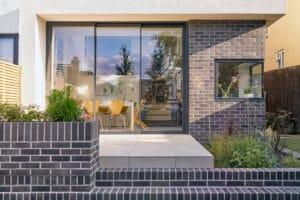 IDSystems theEDGE2.0 sliding doors - narrow 3-panel doors on modern grey brick extension