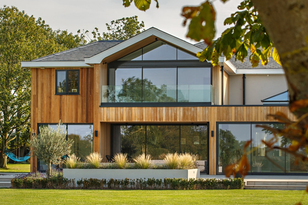 IDSystems theEDGE2.0 sliding doors - The master bedroom of this countryside home features a 3-panel set of doors with gable end glass above leading out on to a large balcony