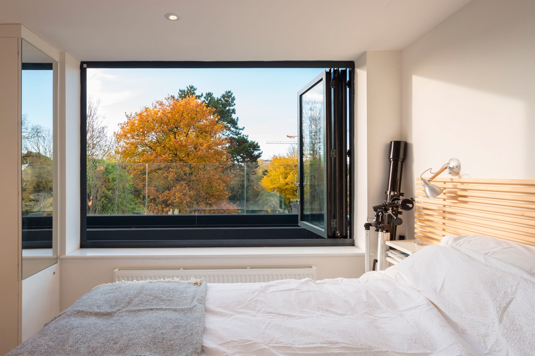 This bifold window allows the master bedroom in a loft conversion to enjoy stunning views over the roof tops of Cambridge