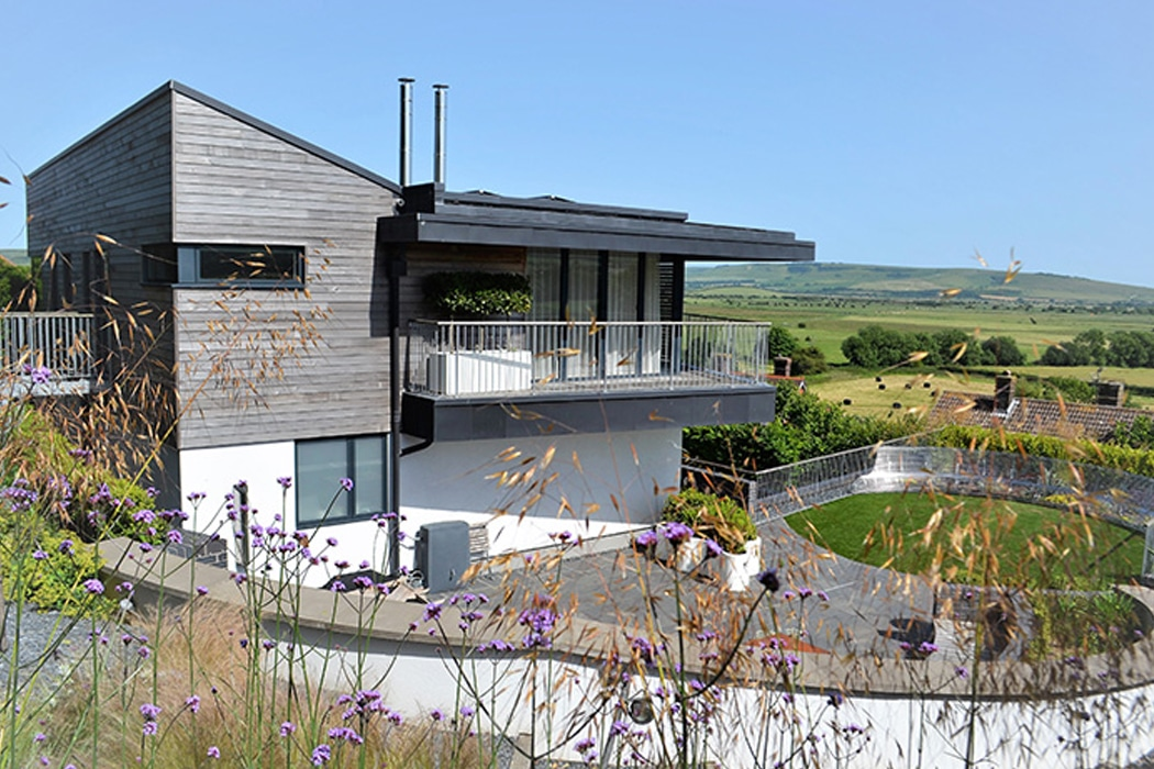 The corner-opening SF55 bifold doors provide stunning views over the rolling South Downs