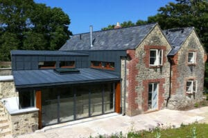 This 19th Century stone cottage has been transformed with a modern extensuin including a 5-panel set of Heritage bifold doors
