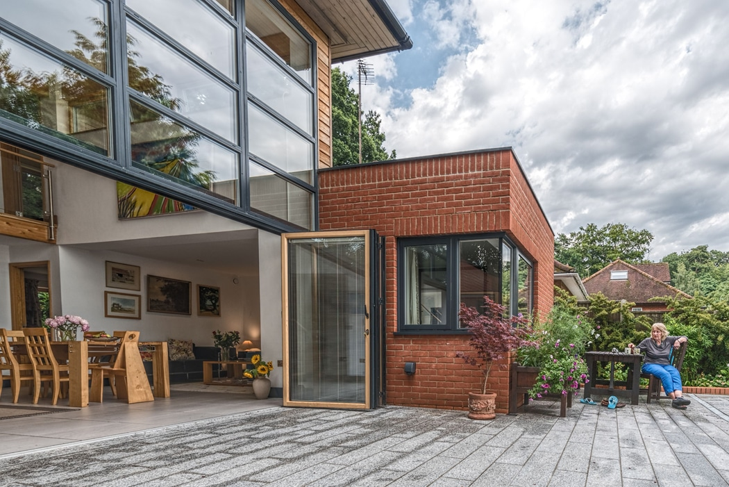 SF75c timber-clad aluminium bifold doors connect this house with patio and pool