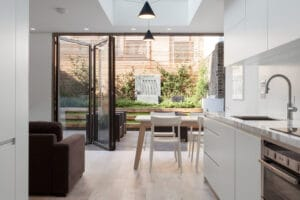 Are bifold doors a good idea? 3-panel bifold doors connect white kitchen with garden